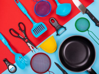 Different kitchen utensils for cooking in kitchen isolated on colored background